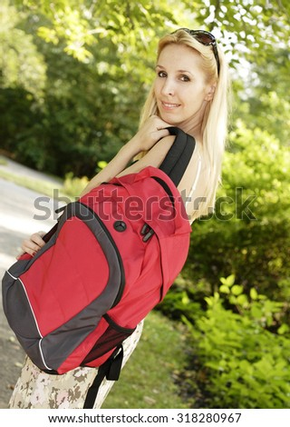 Beautiful woman in park with backpack, shot at angle.