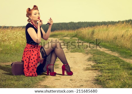 Beautiful woman in pin up sitting on the side of a rural road painting lipstick. - stock photo