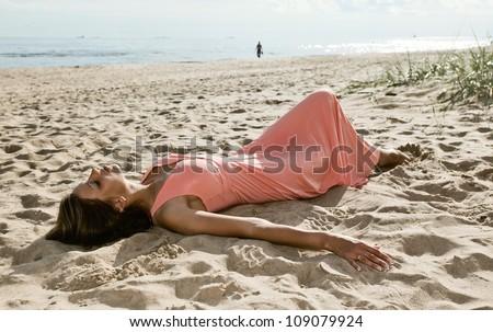 beautiful woman in pink dress on seacoast - stock photo