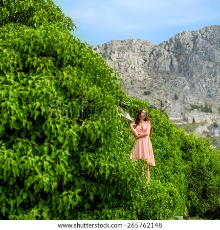 Beautiful woman in pink dress standing in green ivy with mountains on background - stock photo