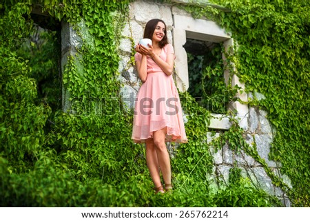 Beautiful woman in pink dress standing with coffee cup on the balcony of green house - stock photo