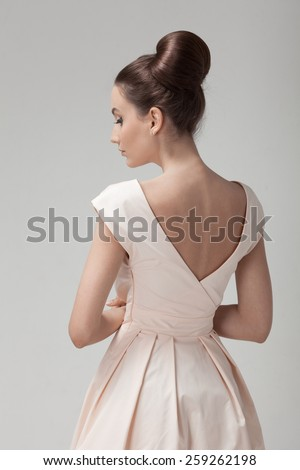 Beautiful woman in pink retro dress. Gray background. - stock photo