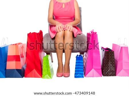 Beautiful woman in pink sitting on chair with colorful shopping bags, commerce lifestyle concept.