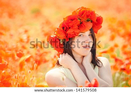 Beautiful woman in poppy wreath in summer poppy field. Outdoor portrait.