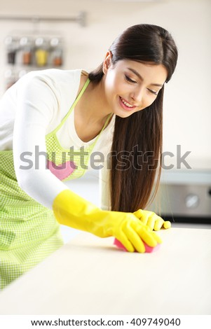 Beautiful woman in protective gloves cleaning kitchen table with sponge - stock photo
