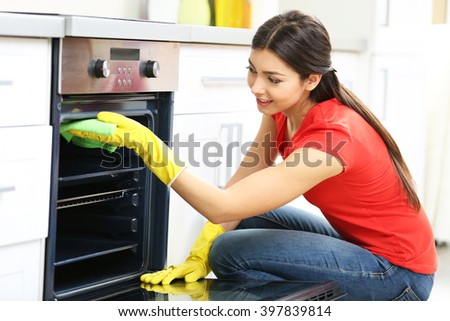 Beautiful woman in protective gloves cleaning oven with rag - stock photo