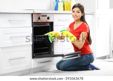 Beautiful woman in protective gloves cleaning oven with rag and spray - stock photo
