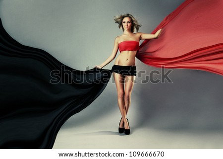 Beautiful woman in red and black waving fabric