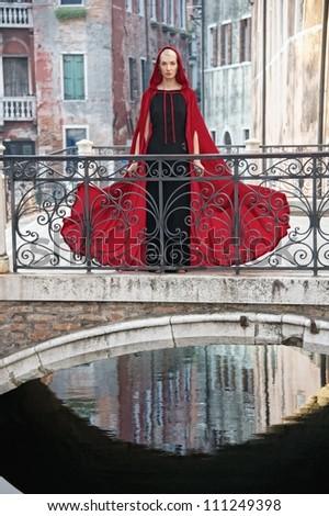 Beautiful woman in red cloak on a bridge - stock photo