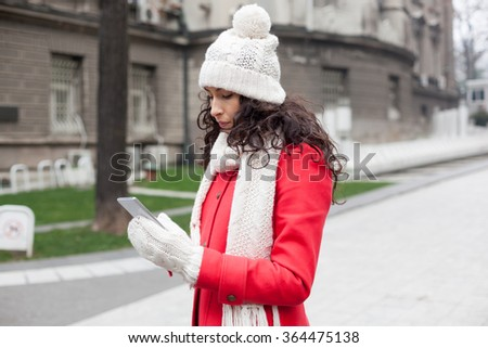 Beautiful Woman in Red Coat and and wool cap and gloves read messages on smartphone. Urban Space. Cold Weather - stock photo