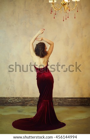 Beautiful woman in red dress and with long hair poses in studio, back view - stock photo