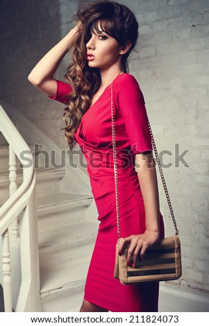Beautiful woman in red dress holding handbag standing on stairs against white brick wall