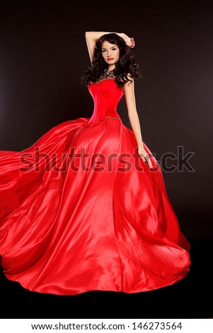 Beautiful woman in red dress isolated on black background. Studio photo. Fashion. - stock photo