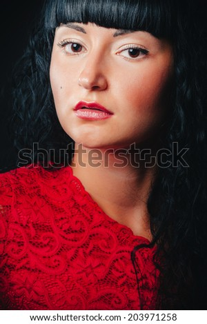 Beautiful woman in red dress isolated on black background. Studio photo. Woman with beauty long brown hair and red lips, red dress- posing at studio.  - stock photo