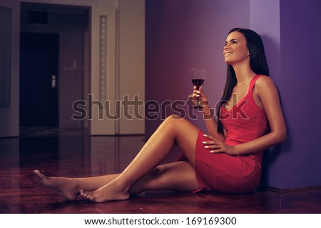 Beautiful woman in red dress sitting on the floor and holding a glass of wine - stock photo