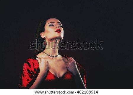 Beautiful woman in red dress with professional make up studio - stock photo