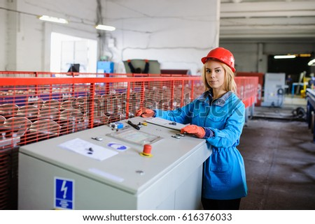 beautiful woman in red safety helmet work as industrial worker at metal sheet profiling mechine at manufacturing factory
