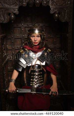 Beautiful woman in roman helmet and armour sitting in a dark interior