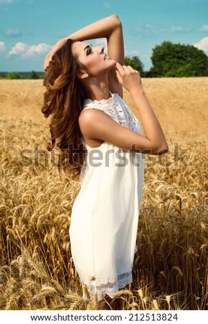 Beautiful woman in rye field wearing white dress. Rural lifestyle  - stock photo