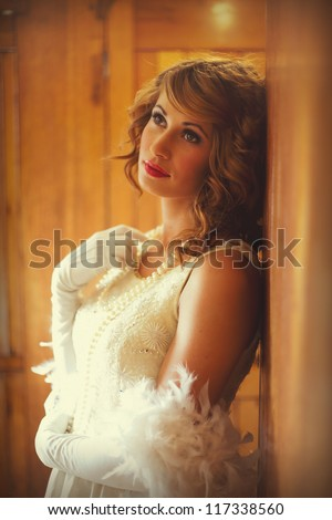 Beautiful woman in 1920s flapper dress standing in a train carriage leaning against wood panelling - stock photo
