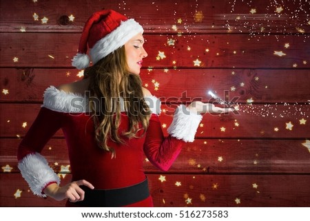 Beautiful woman in santa costume blowing a kiss against wooden background