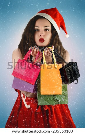 Beautiful woman in Santa costume with santa claus hat with shopping bags. Blowing a kiss and snow. Christmas / New Year shopping. - stock photo