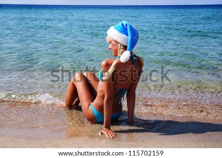 Beautiful woman in santa hat on the sand sea shore