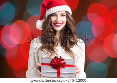 Beautiful woman in santa hat over christmas lights.