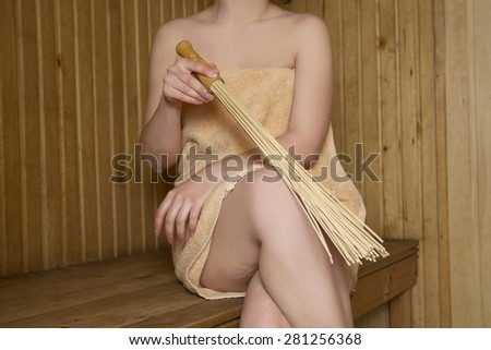 Beautiful woman in sauna, bath accessories. Wooden bucket and sticks - stock photo