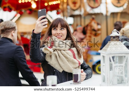 beautiful woman in scarf drinks mulled wine and  makes a selfy on mobile phone on christmas market