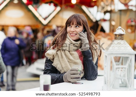 beautiful woman in scarf drinks mulled wine and talks on mobile phone on christmas market