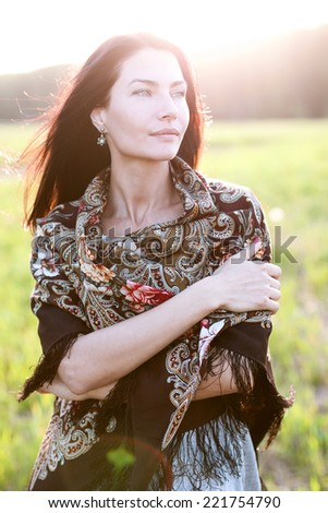 Beautiful woman in scarf outdoors - stock photo