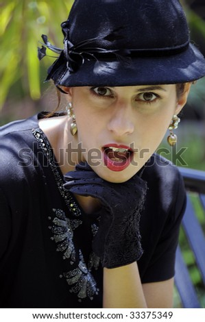 Beautiful woman in sequined black dress with black hat, in front of tropical foliage - stock photo