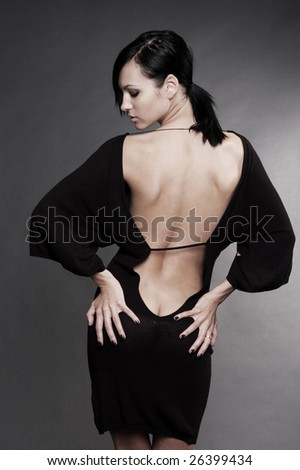 beautiful woman in sexy evening dress against dark background - stock photo