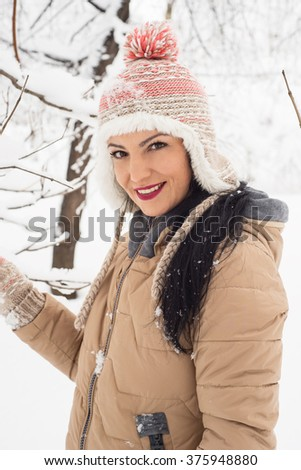 Beautiful woman in snow posing  and smiling to camera - stock photo