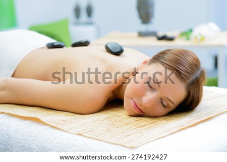 beautiful woman in spa salon during a stone therapy