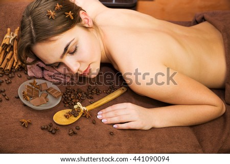 Beautiful woman in spa salon having chocolate therapy procedure with coffee seeds, cinnamon sticks, star anise  - stock photo