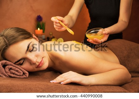 Beautiful woman in spa salon having spa therapy honey procedure with hands of masseur - stock photo