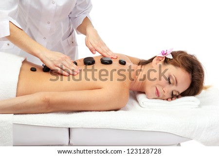 beautiful woman in spa salon with spa stones  getting massage, isolated on white