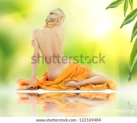 beautiful woman in spa with towels over green - stock photo