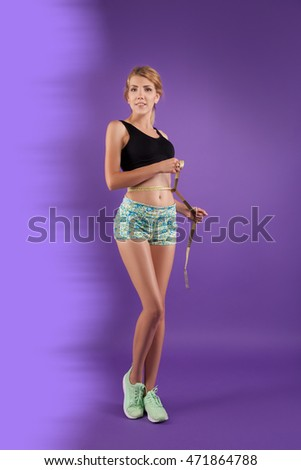 Beautiful woman in sports clothes and shoes, posing at the camera, studio. WOMAN and centimeters
