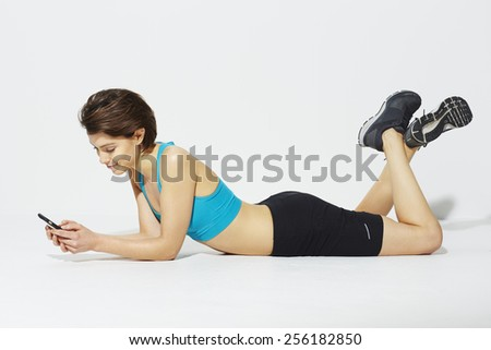 Beautiful woman in sportswear using cell phone