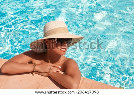 Beautiful woman in straw hat posing by the pool, summer day, outdoor - stock photo