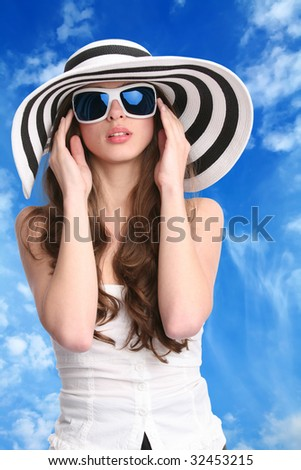 beautiful woman in striped hat and sunglasses with hands near face on background of the blue sky