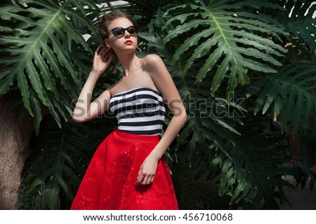 Beautiful woman in stylish clothes, the background of palm trees and vines, jungle. WOMAN IN THE TROPICS.Stylish woman in jungle.BRIGHT WOMAN ON THE BACKGROUND OF THE JUNGLE.Woman in sunglasses. - stock photo