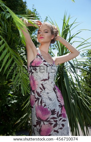 Beautiful woman in stylish clothes, the background of palm trees and vines, jungle. WOMAN IN THE TROPICS