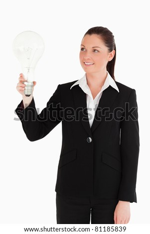 Beautiful woman in suit holding a light bulb while standing against a white background - stock photo