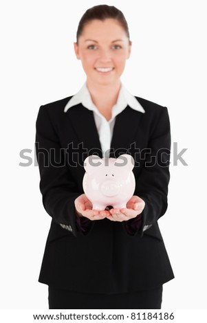 Beautiful woman in suit holding a pink piggy bank while standing against a white background - stock photo