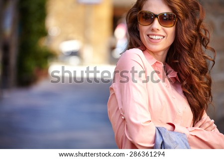 beautiful woman in summer dress walking and running joyful and cheerful smiling in Tuscany, Italy.  - stock photo