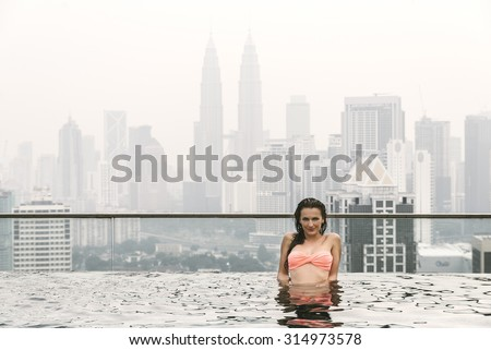 Beautiful woman in swimming pool watching the city. Kuala Lumpur with Twin Towers - stock photo